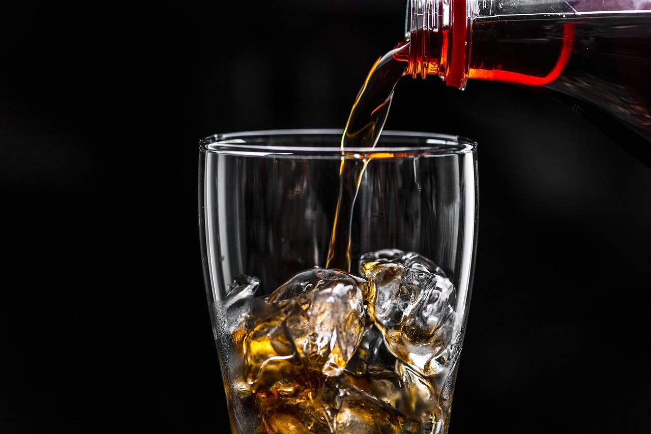 Foto: Cola, die in ein Glas mit Eiswürfeln eingeschenkt wird