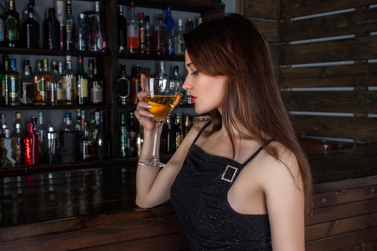 Foto: junge Frau, in einer Bar einen Cuba Libre trinkend
