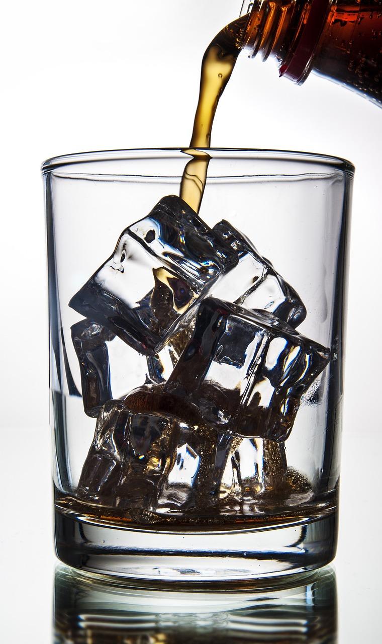 Foto: Cola, die in ein Glas mit Eiswürfeln eingegossen wird