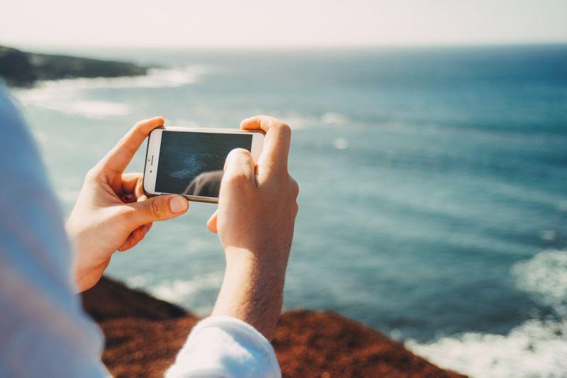Foto: jemand, der mit dem Smartphone ein Foto vom Meer macht