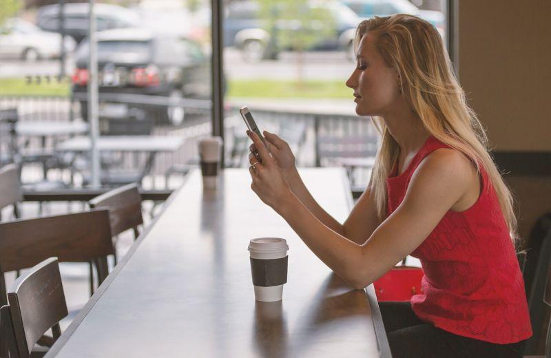 Foto: Frau benutzt mobiles Internet in Bar