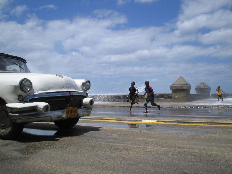 Foto: Oldtimer im Vordergrund, im Hintergrund auf dem Malecon spielende Kinder